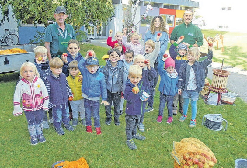 Kita-Kinder pressen Äpfel
